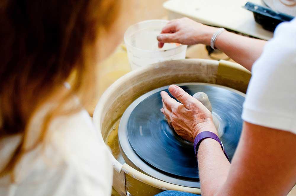 Adulte qui montre comment faire des poteries à un enfant