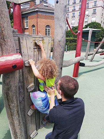 Petite fille grimpant sur une structure de jeu
