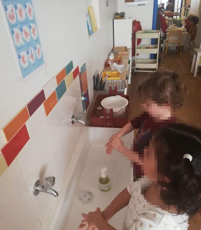 Enfants se lavant les mains tout seul devant le lavabo